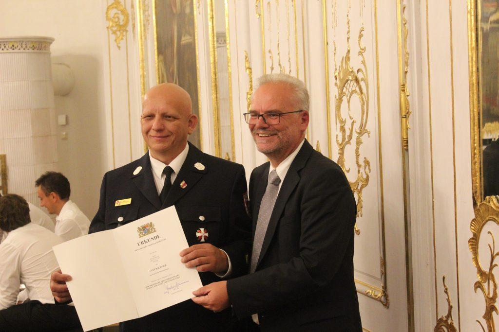 1. Kommandant Herr Helmut Motzer wird von Regierungspräsident Dr. Erwin Lohner die Urkunde zur Verleihung des Steckkreuzes übergeben